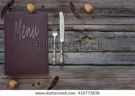 Vintage leather restaurant or cafe food menu with silverware or cutlery including a fork and a knife on a rustic wood table background