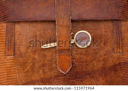 Vintage leather textured background with magnifying glass - stock photo