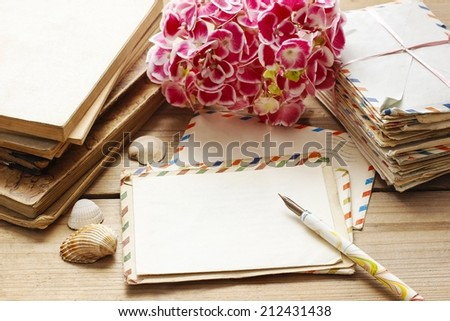 Vintage letters, books and bouquet of pink hortensia flowers in the background - stock photo