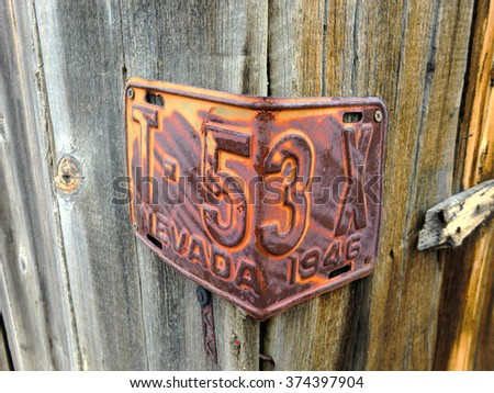 Vintage license plate with rust on wooden wall - landscape photo - stock photo