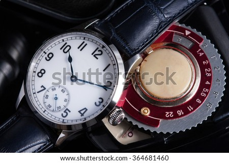 Vintage look marine watches with white dial, and arabic numbers, blued hands, onion crown on blue alligator leather strap soviet photo exposure meter mechanism on black background - stock photo
