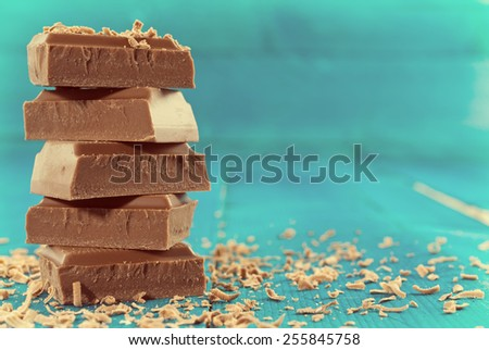 Vintage look of roughly cut chunks of a chocolate bar and chocolate shavings on wooden background - stock photo