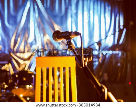 Vintage looking A microphone on an empty stage before a concert - selective focus on the mic with blurred background - stock photo