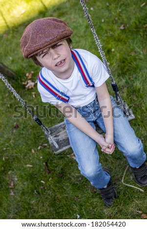vintage looking boy sitting on a swing - stock photo