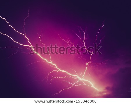 Vintage looking Bright lightning bolt over dark violet sky - stock photo
