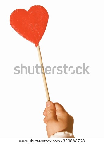 Vintage looking Child's hand holding an heart shaped lollipop, with copyspace