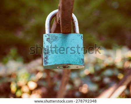 Vintage looking Love lock padlock sweethearts locked to a fence to symbolize eternal love - stock photo