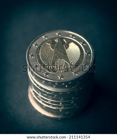 Vintage looking Pile of German 2 Euro coins over black - stock photo