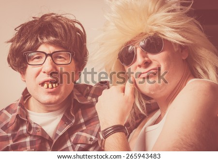 Vintage looking portrait of two wild and crazy guys wearing wigs and fake teeth.