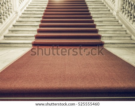 Vintage looking Red carpet on a stairway used to mark the route taken by heads of state, vips and celebrities on ceremonial and formal occasions or events