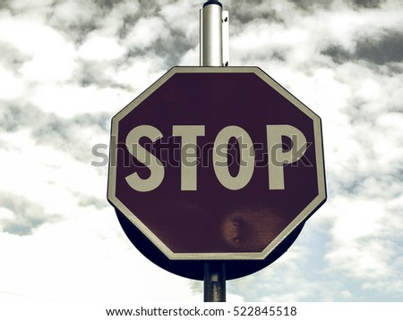 Vintage looking Stop traffic sign over blue sky with clouds