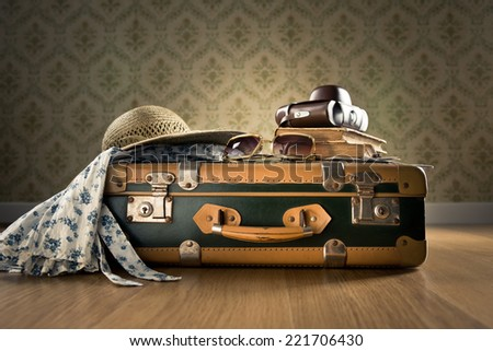Vintage luggage with sunglasses, camera and straw hat on wooden floor. - stock photo