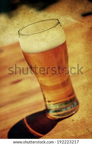 vintage macro shot of glass with cold beer on wooden table