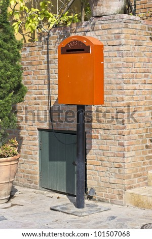 Vintage mailbox in front of brick wall - stock photo