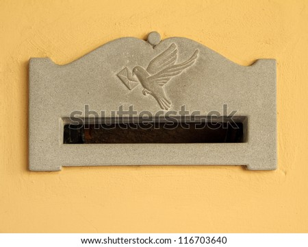 vintage mailbox with slot in wall and decorative relief with pigeon arriving with envelope in his beak, Italy, Europe - stock photo