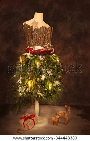 Vintage mannequin dressed for a festive Christmas with gift and deer - stock photo
