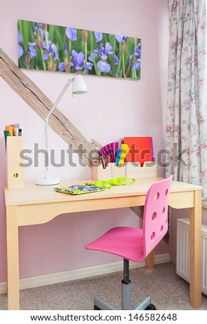 Vintage mansion - a schoolgirl's desk by a pink wall - stock photo