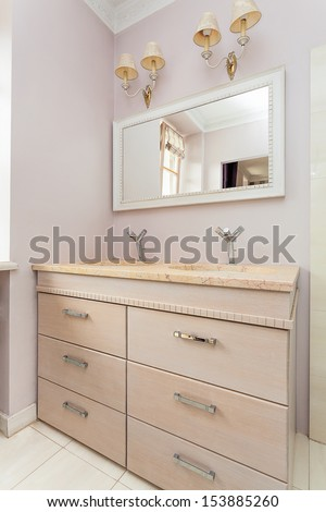 Vintage mansion - a stone washibasin on a chest of drawers, a mirror and lamps - stock photo
