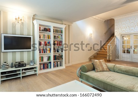 Vintage mansion - a striped wall with a tv set and a white bookshelf - stock photo