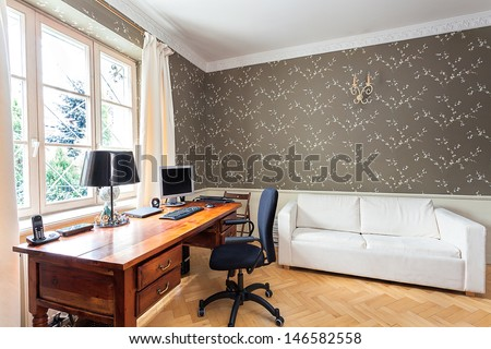 Vintage mansion - office with a wooden desk and a white couch - stock photo