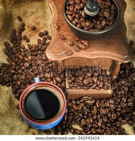 Vintage manual coffee grinder with coffee beans and cup - stock photo