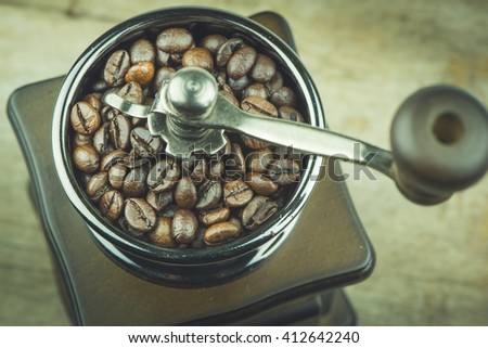 Vintage manual coffee grinder with coffee beans on the wooden backgrounds. - stock photo