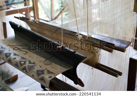 Vintage manual weaving loom with unfinished textile work - stock photo