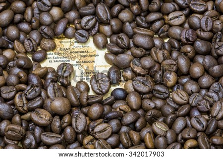 Vintage map of Central America covered by a background of roasted coffee beans. Guatemala, Honduras, Nicaragua, El Salvador and Costa Rica are between the main producers and exporters of coffee.