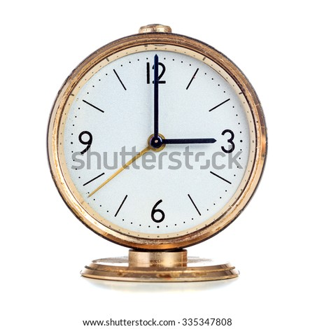 Vintage mechanical alarm clock showing three o'clock isolated over white - stock photo