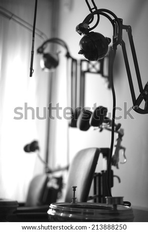 Vintage medical clinic; dentist's chair and equipment; monochrome - stock photo