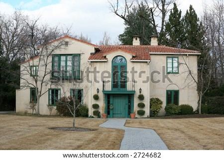Vintage Mediterranean style house from the front with golden grass and clouds - stock photo