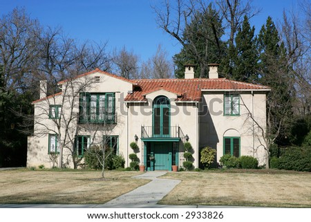 Vintage Mediterranean style house from the front with golden grass and clouds