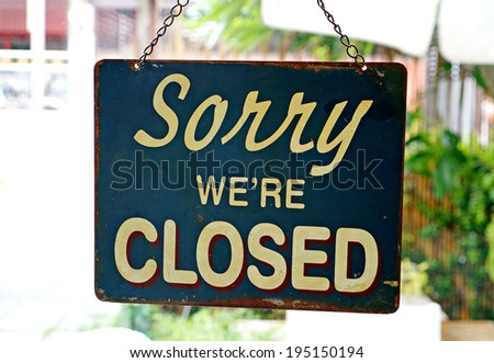 Vintage metal closed sign on shop door with nature background. (Sorry we're closed)