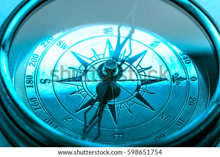 Vintage metal compass in toning light closeup