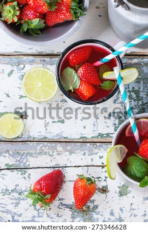 Vintage metal cups with retro cocktail tubes and water-cans of homemade strawberry lemonade, served with fresh strawberries, mint and lime over old white wooden table. View from above - stock photo