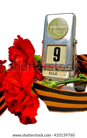 Vintage metal desk calendar with 9th May date and George ribbon with red carnations bouquet -  Victory Day concept isolated on white background. Selective focus at the calendar. 9 May concept.  - stock photo
