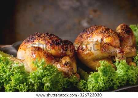 Vintage metal dish with two grilled chicken and green salad over old wooden table. Dark rustic style. - stock photo