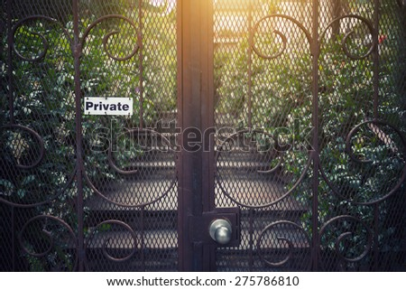 Vintage metal gate with private sign and garden view in background. - stock photo