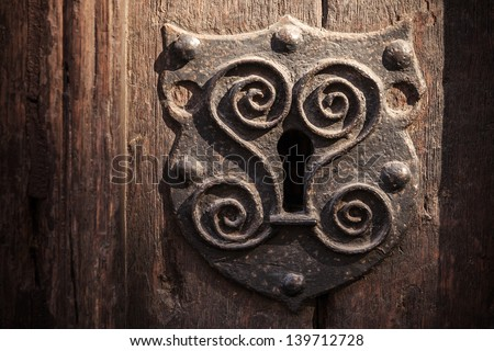 Vintage metal keyhole decorative element on weathered wooden surface