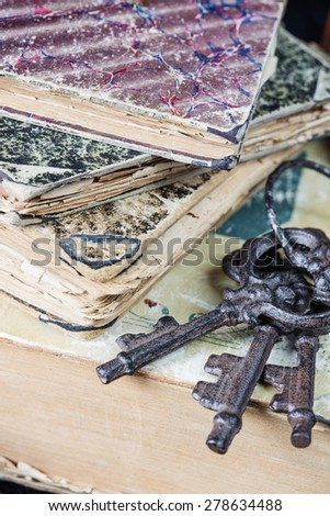 Vintage metal keys and the old books covered with shabby hardcover - stock photo