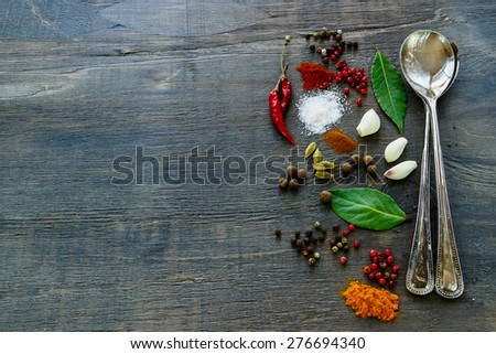 Vintage metal spoons with herbs and spices selection on dark wooden table. Background with space for text. - stock photo