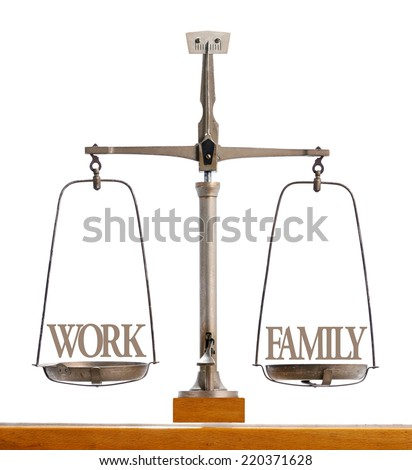 Vintage metallic weighing scale showing perfect balance between work and family, on a wooden table, with copy space on white - stock photo