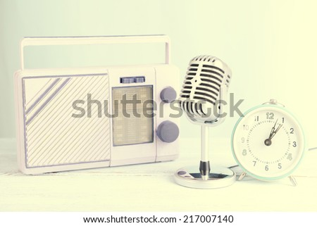 Vintage microphone,alarm clock and radio on table on light background - stock photo