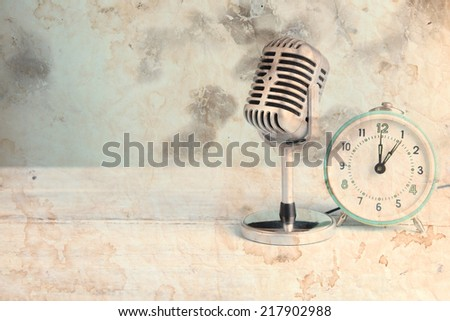 Vintage microphone and alarm clock on table - stock photo