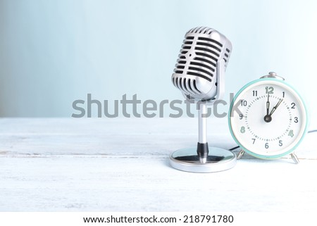 Vintage microphone and alarm clock on table on light blue background - stock photo