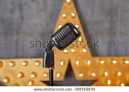 Vintage microphone in studio with star on background - stock photo