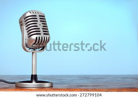 Vintage microphone on the table with cyanic background - stock photo