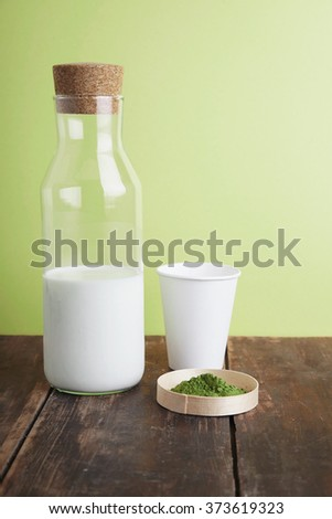 Vintage milk bottle, white paper take away glass and organic premium matcha tea powder on brown brushed wooden table in front of green simple background