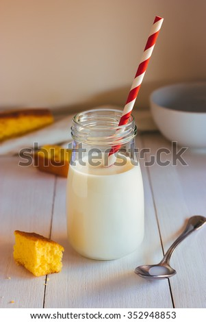 Vintage milk bottle with red striped drinking straw and pieces of sponge cake on white wooden table