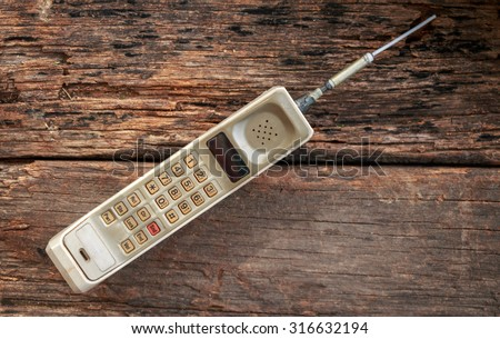 vintage mobile phone on wooden background (vintage style) - stock photo
